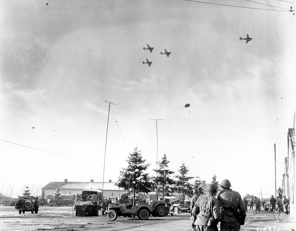 Photo taken by a U.S. Army Signal Corps photographer on 26 December 1944 in Bastogne, Belgium as troops of the 101st Airborne Division watch C-47s drop supplies to them. Jeeps and trucks are parked in a large field in the near distance.