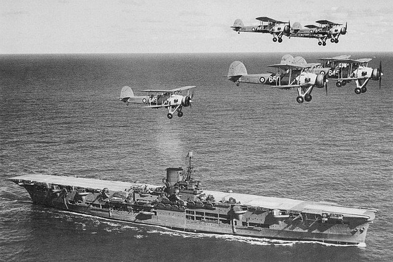 "British aircraft carrier Ark Royal with a flight of ""Swordfish"" overhead, circa 1939. Courtesy of Donald M. McPherson, 1977. Image via Wikimedia Commons. (For illustrative purposes)"