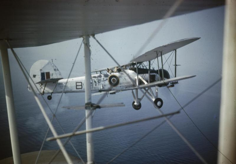 Close-up of a Fairey Swordfish Mark II, HS 545 'B', in flight as seen through the struts of another aircraft, probably while serving with No 824 Squadron, Fleet Air Arm, 1943-1944. By British official photographer [Public domain], via Wikimedia Commons. IWM: TR1138.