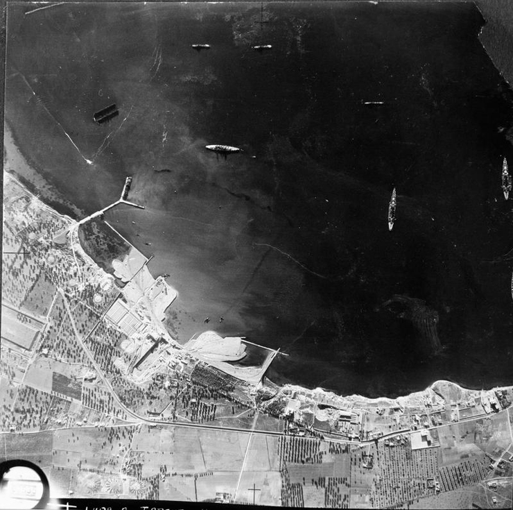 Aerial-reconnaissance vertical of Italian naval vessels moored in the outer harbour (Mar Grande) at Taranto, Italy. The floating dock and 'Y' jetty can be seen at left, and also a large dock under construction at lower left. Photograph taken by No. 431 Flight RAF flying from Luqa, Malta. By No. 431 Flight RAF [Public domain], via Wikimedia Commons. IWM MH 8052.