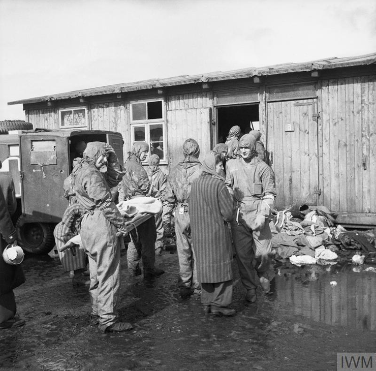 Wearing protective clothing, men of 11 Light Field Ambulance, Royal Army Medical Corps evacuate inmates from one of the huts at Belsen. © IWM (BU 4196)