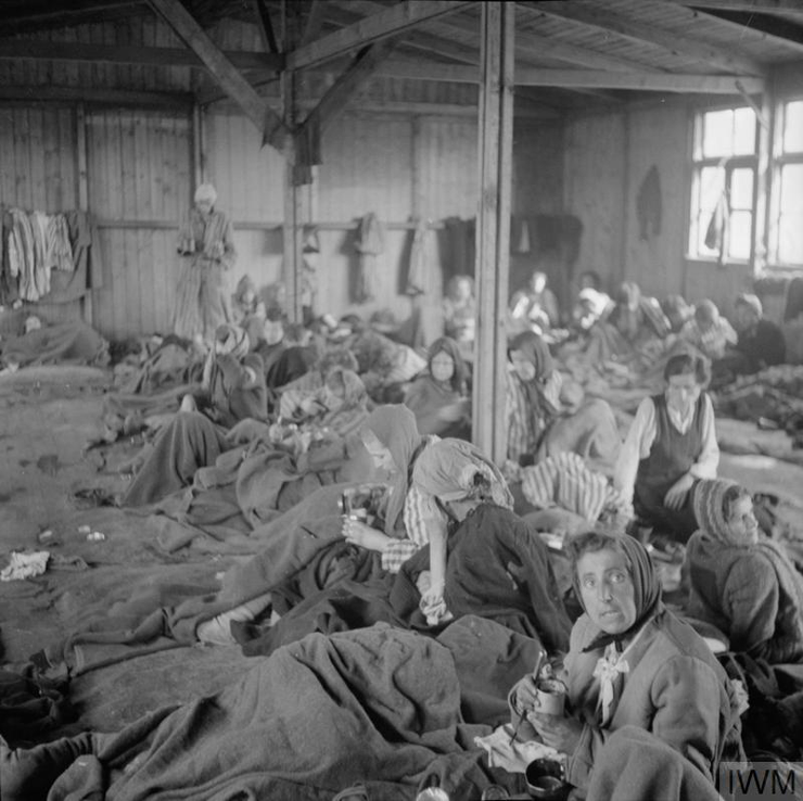 Women inmates suffering from typhus receive drinking water in one of the camp huts. © IWM (BU 4017)