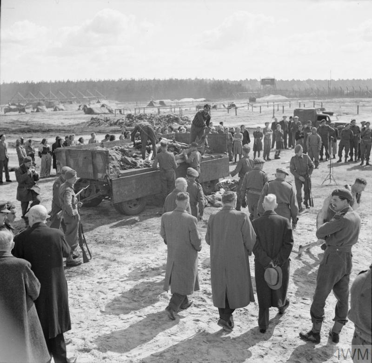 Camp inmates watch German SS guards load a lorry with bodies of the dead. In the foreground, British Army officers escort a party of civilian visitors to the camp. © IWM (BU 4255)